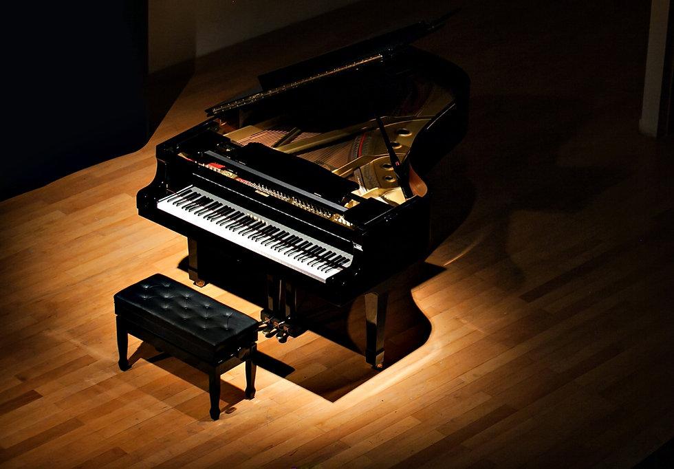 black grand piano at spot light in dark