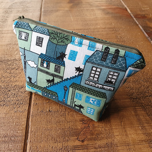 Cosmetics bag with small black cats on a blue cityscape background