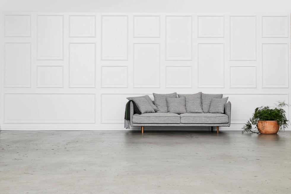 004_Panelvæg_med_betongulv_sofa_og_bloms