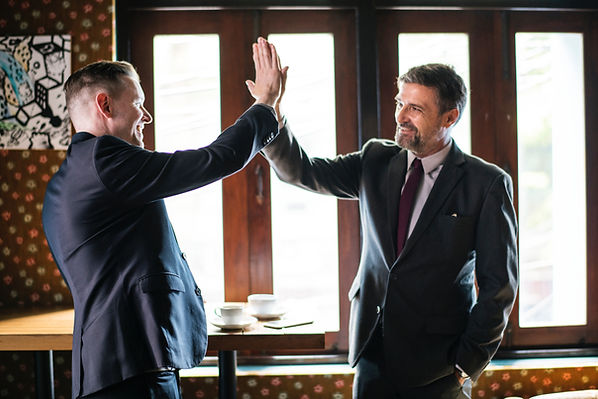 two business leaders high five celebrating success