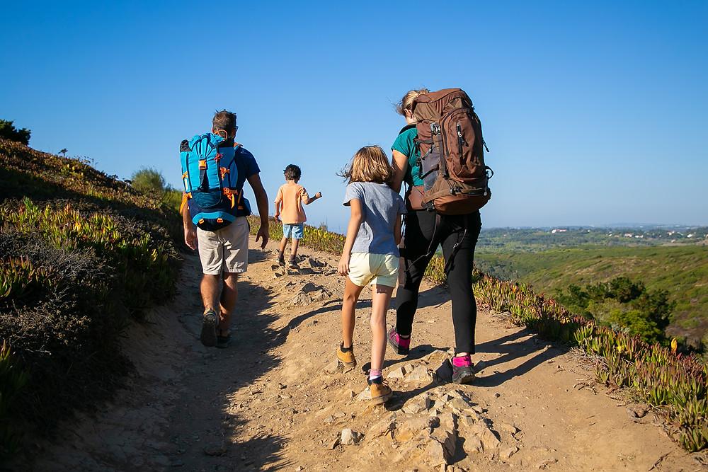 família (pai, mãe e um casal de crianças) fazendo trilha