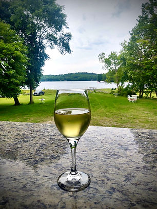 A glass of wine on the covered back deck of Tighe's Bistro Amricain.