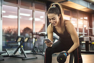 Young woman using phone in gym..jpg