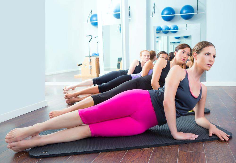 נשים צעירות בסטודיו שוכבות על מזרון לתרגול שרירי הירכיים