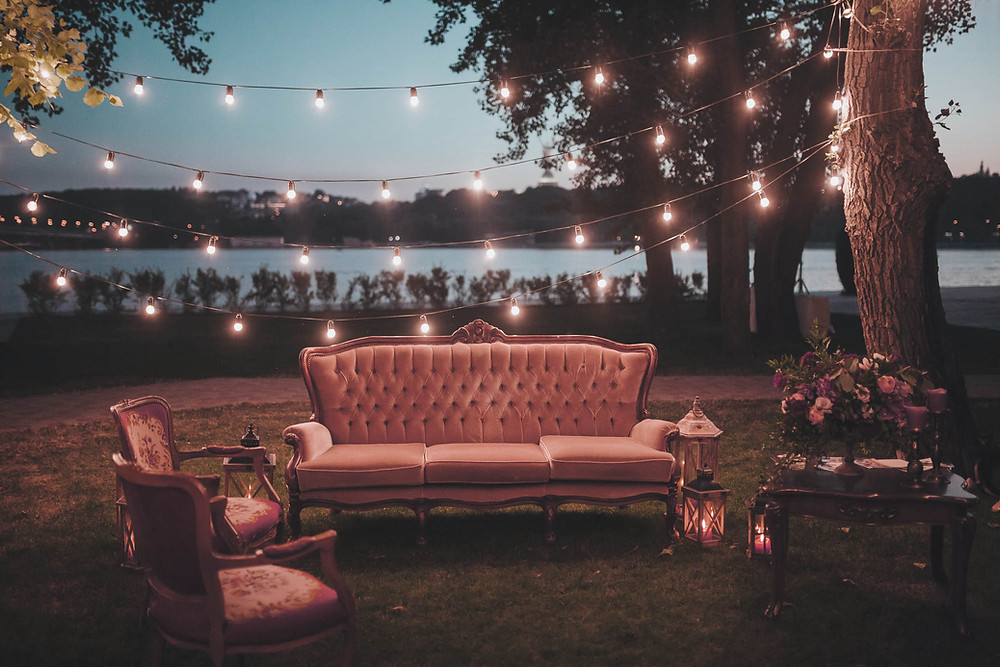 Royal looking sofa set outside with lights strung on trees around dusk