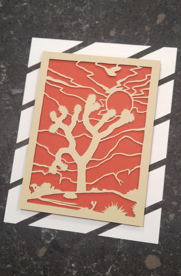 Finished papercut of the sun setting behind a joshua tree