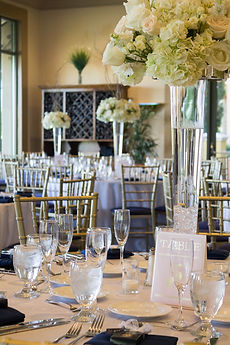 White hydrangea, cream and white roses with s[ray roses on a clear glass riser.