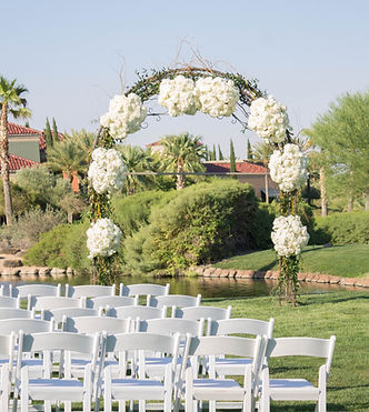 White hydrangeas and roses with curlly willow and Italian ruscs on wedding arch.