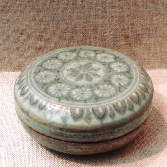 Boîte à fard à décor incrusté de rosettes et bordure de lotus, XIIIeme siècle. Barbotine blanche et noire sous couverte céladon