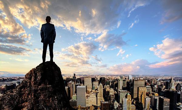 business man high perch overlooking city