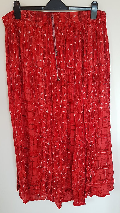 Red patterned long skirt with small bells on ties.