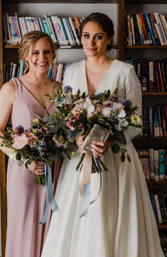 bride and her bridesmaid getting ready to start the michigan indoor church wedding ceremony coordinated by tascha amond lead wedding planner of muse wedding located in grand rapids michigan