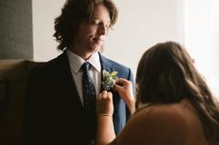 groomsmen girlfriend is pinning his boutonniere