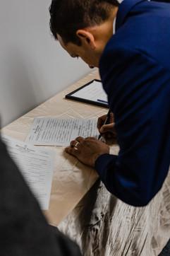 groom signing marriage license at michigan church wedding