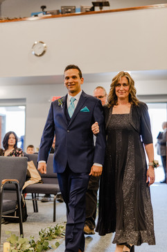 groom coming in being escorted by his mother to his wedding ceremony