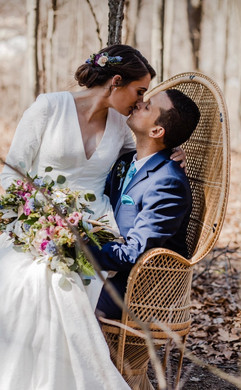 couple kissing on boho chair in the woods for couples portraits at their michigan wedding.