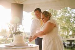 lexie and dan cutting their wedding cake in their backyard tented wedding