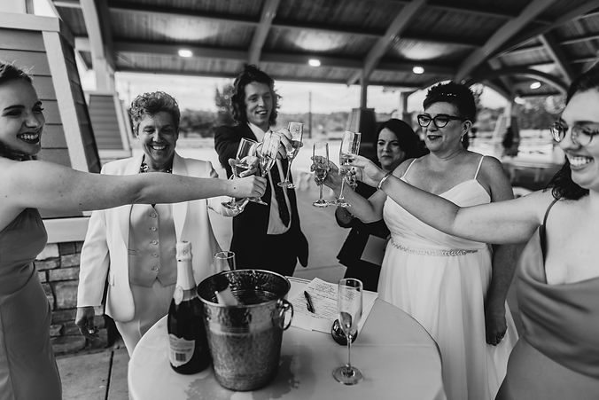 wedding party cheersing after signing the marriage license after their outdoor lgbtq wedding ceremony in michigan