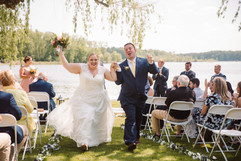 couple exit their wedding ceremony smiling and jumping