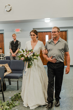 bride walking down the aisle escorted by her father door being held open by michigan wedding planner and wedding coordinator tascha amond