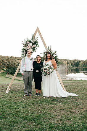 Tascha Amond, owner and lead planner of muse weddings. A grand rapids, michigan based wedding planning and wedding coordination company smiling and hugging the bride and groom