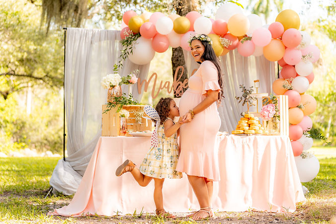 daughter kissing moms belly at a michigan baby shower planning party