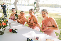 bridesmaids posing with a bottle of champagne