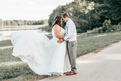 bride with a flowy dress overlooking water in the arms of the groom