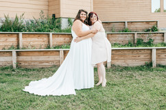 bride and her maid of honor hugging and laughing