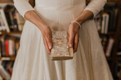 bride holding family heirloom, a family bible at her indoor michigan wedding