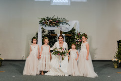 bride and her daughters posing in a photo at their michigan church wedding