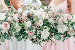bridesmaids and bride showing off their beautiful pink and green and white bouquets designed by mitten floral