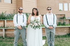 bride taking picture with the groomsmen on her summer michigan wedding day!