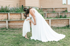 bride and her daughter the flower girl posing together and kissing