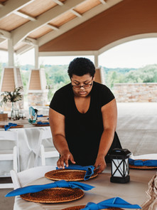 Wedding coordinator assistant setting up table setting