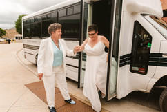 brides getting off the affordable limousine party bus