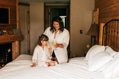 bride and her daughter drinking OJ while getting ready for their wedding