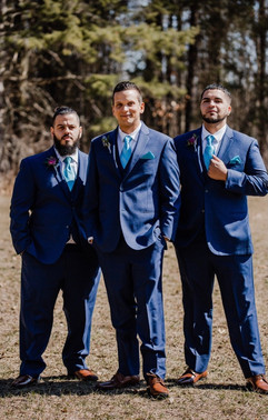 groom and his groomsmen hanging out and posing outside near the woods at a michigan wedding