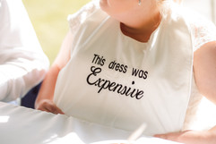 """bride wearing a bib over her wedding dress during dinner. It says """"this dress was expensive"""""""