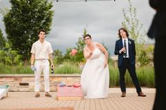 bride playing cornhole at lgbtq wedding