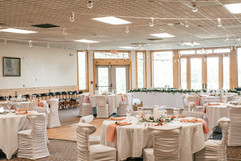 indoor wedding reception pink and white with chair covers, draped globe lighting and light pink napkins