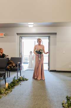 bridesmaid coming down the aisle at their church wedding ceremony