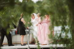 mikchigan wedding planner tascha amond of muse weddings is helping the bride out of a boat for her lakefront wedding
