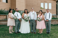 bride, groom and their wedding party smiling and posing for photos