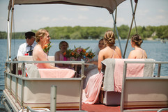 bridesmaid and bride riding on a boat on their way to a michigan lakefront wedding