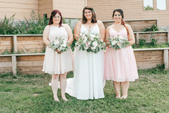briude and her bridesmaid with dusty rose dresses and pink and white bouquets