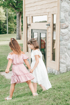 flower girl and her cousin, two little girls holding hands and walking in a field at a michigan wedding