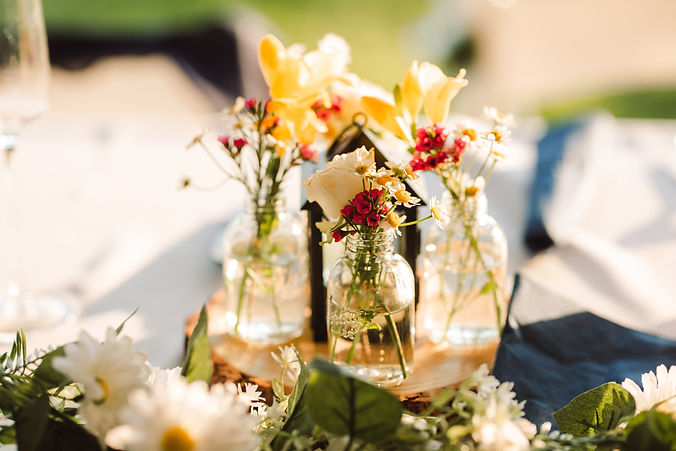 sun hitting the beautiful pink and yellow centerpieces for outdoor tented wedding in michigan