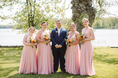 groom posing with bridesmaids at his michigan wedding on the lakefront