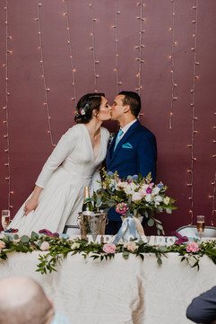 couple kissing at their sweetheart table